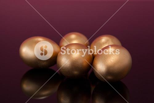 Golden Easter eggs on colored background
