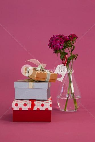 Stack of gift boxes and flowers vase