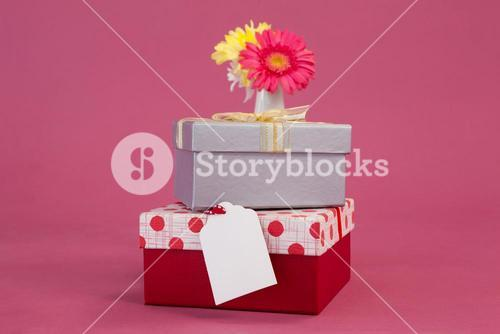 Stack of gift boxes with tag and flowers