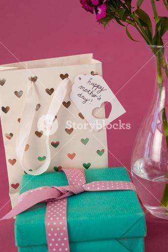 Close-up of gift box, paper bag and flowers vase