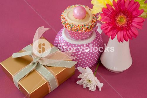 Close-up of gift box, cupcake and flowers vase