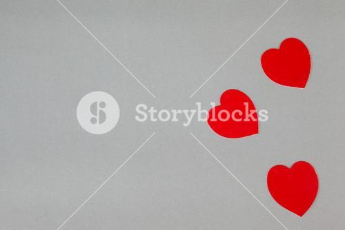 Three red hearts on grey background