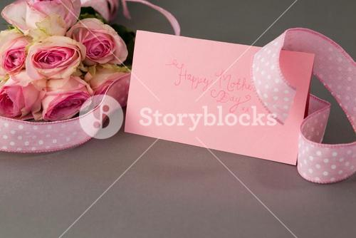 Close-up of happy mothers day card and flowers