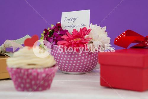 Cup cake, gift box and fresh flowers on wooden surface