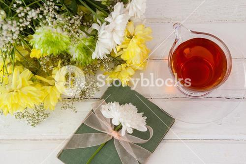 Cup of tea with flowers and book on table