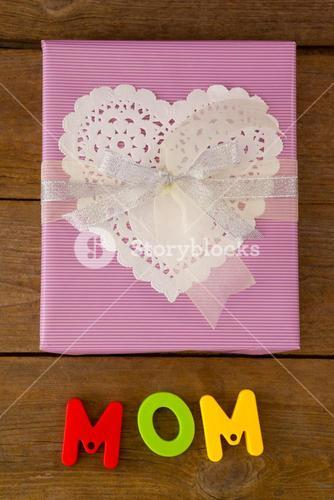 Gift box with alphabets reading mom against wooden background