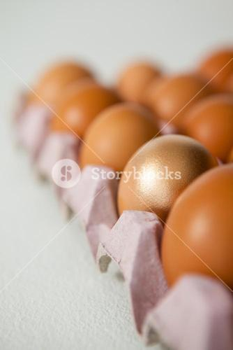 Easter eggs in carton on white surface