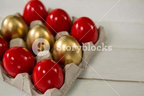 Close-up of red and golden Easter eggs in the carton