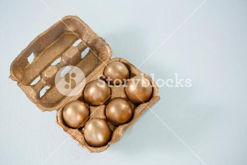Close-up of golden Easter eggs in the carton