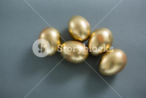 Golden Easter eggs on grey background
