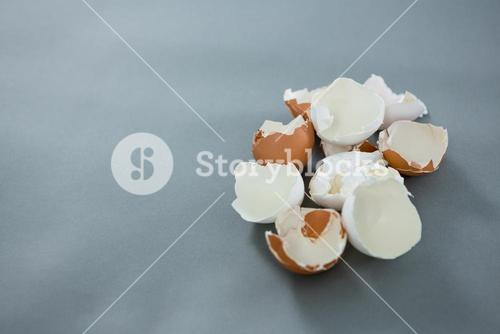 Broken brown egg on grey background