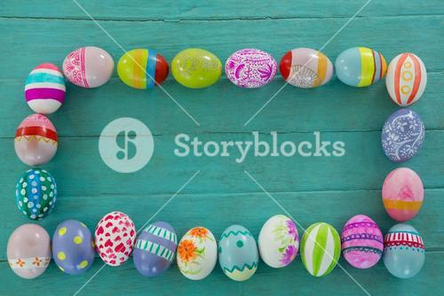 Painted Easter eggs arranged in rectangle shape on wooden plank