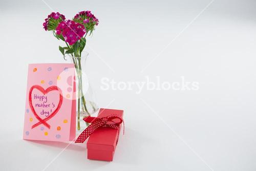 Happy mothers day greetings with gift box and flower vase