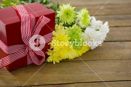 Gift box and bunch of yellow flowers on wooden plank