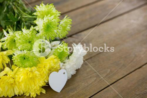 Bunch of yellow flowers with heart shape tag on wooden plank