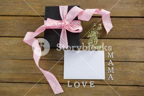 Gift box with mama love text on wooden plank