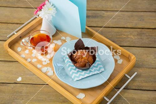 Cupcake, tea, flower vase and card in tray