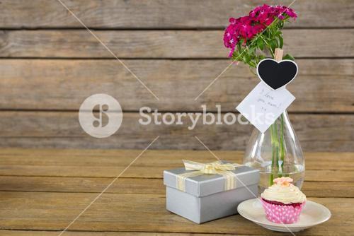 Gift box and flower vase with cupcake in plate on wooden plank