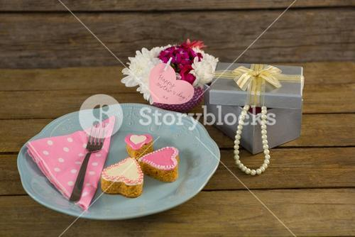 Open gift box with flower vase and heart shape cookies