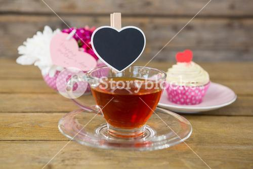 Cupcake, tea, flower vase and happy mothers day greetings card in tray