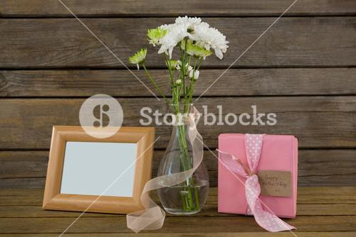 Gift box, photo frame and flower vase on wooden surface