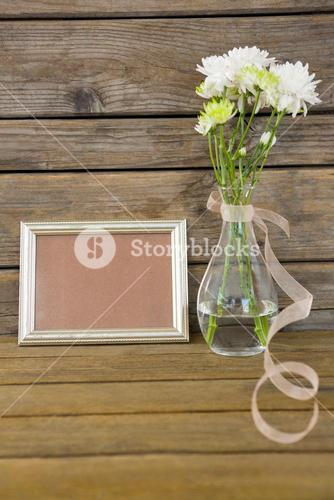 Photo frame and flower vase on wooden surface