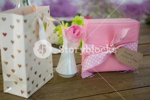 Gift bag, gift box and flower vase on wooden surface