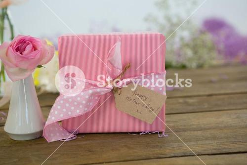 Gift box and flower vase on wooden surface