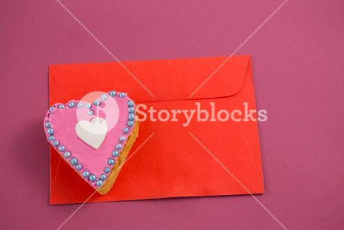 Heart shape cookie on red envelope against pink background