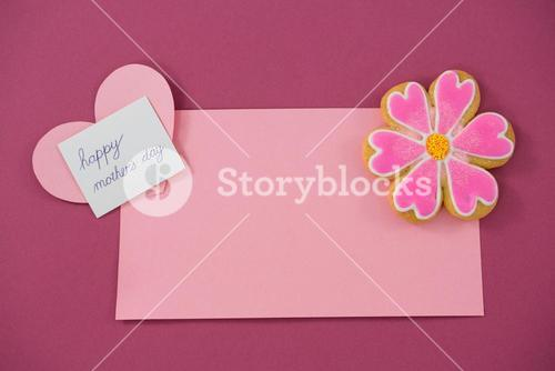 Flower shape cookie, heart shape card on red envelope against pink background