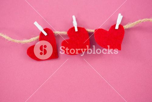 Red hearts with cloth peg hanging on rope