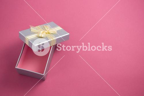 Open gift box against pink background