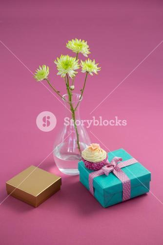 Flower vase and cupcake with gift boxes against pink background