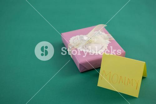 Gift box with text mom on card against green background