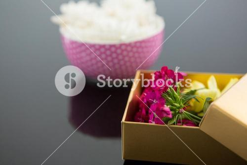 Opened gift box and bowl with flowers