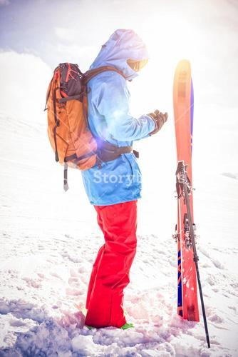 Skier using mobile phone on snowy mountains
