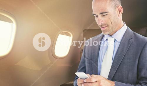 Composite image of confident businessman using cellphone