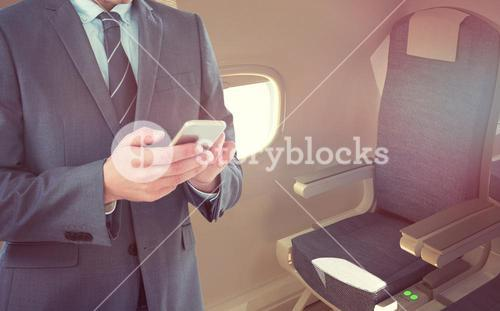 Composite image of smiling businessman using mobile phone