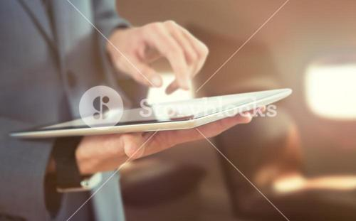 Composite image of midsection of businessman using wireless technology
