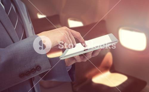 Composite image of midsection of businessman using tablet computer