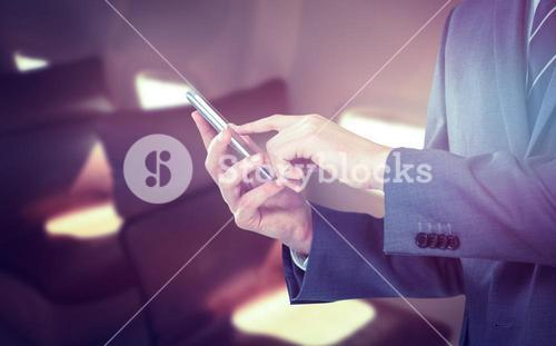 Composite image of midsection of businessman using mobile phone