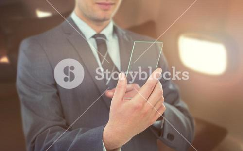 Composite image of businessman using futuristic mobile phone