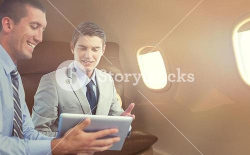 Composite image of businessmen working together with laptop and tablet