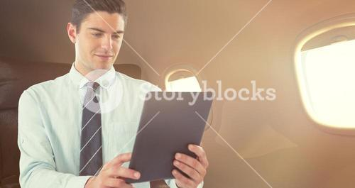Composite image of businessman using digital tablet