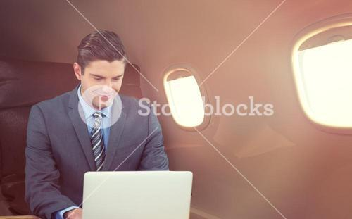 Composite image of happy businessman using laptop at table