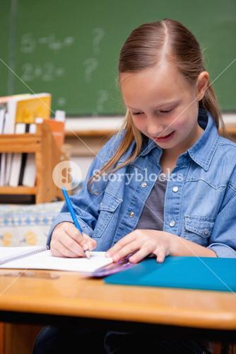 Portrait of a schoolgirl writing
