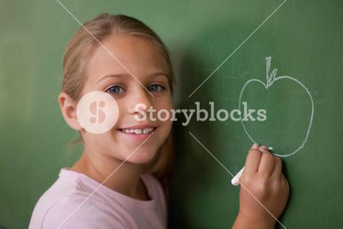 Smiling schoolgirl drawing an apple