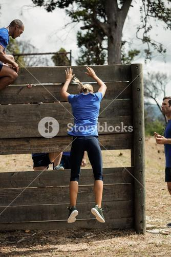 Fit woman jumping off the wooden wall