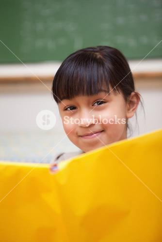Portrait of a smiling schoolgirl reading