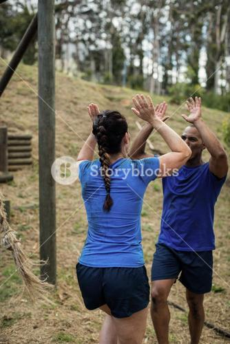Couple giving high five to each other during obstacle course